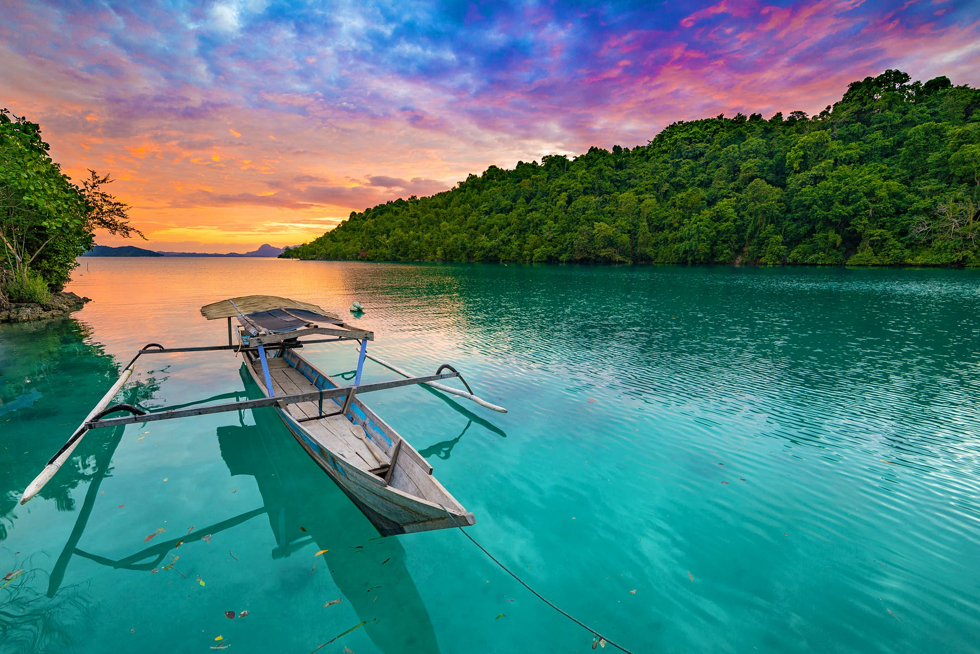 A small boat on still water during sunset at the Togian Islands. ©Fabio Lamanna/Shutterstock