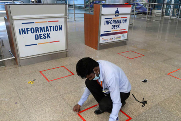 """A worker marks squares on the ground at the Rajiv Gandhi International """"Airport"""" in Hyderabad."""