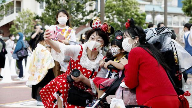 Visitors sport Disney-themed face masks. Kyodo News/AP
