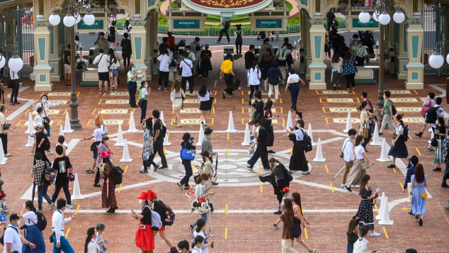 Guests wait in a socially-distant line to get into Tokyo Disneyland on opening day. Philip Fong/AFP/Getty Images