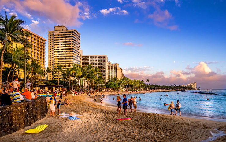 Tourists on the beach front at sunset on Waikiki beach ©Jeff Whyte/Shutterstock